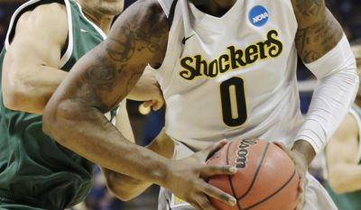 Wichita State forward Chadrack Lufile (0) takes the ball past Cal Poly forward Chris Eversley (33) during the first half of a second-round game in the NCAA college basketball tournament Friday, March 21, 2014, in St. Louis. (AP Photo/Charlie Riedel)