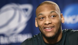 Michigan State's Adreian Payne smiles while answering a question at a news conference before the third round of the NCAA men's college basketball tournament in Spokane, Wash., Friday, March 21, 2014. Michigan State plays Harvard on Saturday. (AP Photo/Elaine Thompson)