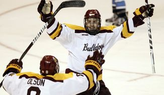 Minnesota-Duluth's Caleb Herbert, top, celebrates his goal with teammate Drew Olson (8) during the second period of a NCAA Northeast Regional college hockey game against Maine in Worcester, Mass., Saturday, March 24, 2012. (AP Photo/Winslow Townson)