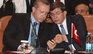 Turkish Prime Minister Recep Tayyip Erdogan, left, and Turkish Foreign Minister Ahmet Davutoglu, right,  look on a cell phone during a meeting  at the  foreign ministry in Rabat, Morocco, Monday, June 3, 2013. On Monday, Erdogan again dismissed the street protests as being organized by extremists, described them as a temporary blip and angrily rejected comparisons with the Arab Spring uprisings. (AP Photo / Abdeljalil Bounhar)