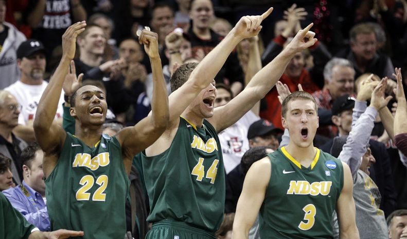 Players on the North Dakota State bench stand and cheer as their team takes the lead against Oklahoma in overtime during a second-round game of the NCAA men's college basketball tournament in Spokane, Wash., Thursday, March 20, 2014. North Dakota State won 80-75 in overtime. (AP Photo/Elaine Thompson)