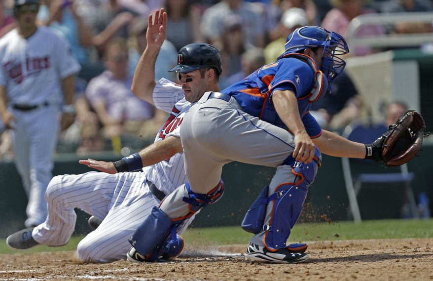 Minnesota Twins Joe Mauer reaches home as New York Mets catcher Taylor Teagarden covers the plate on a sacrifice fly by Wilkin Ramirez in the fourth inning of a exhibition baseball game in Fort Myers, Fla., Friday, March 21, 2014. (AP Photo/Gerald Herbert)