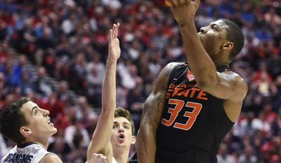 Oklahoma State guard Marcus Smart throws in a left-handed shot as Gonzaga guard Kyle Dranginis defends during the second half in a second-round game in the NCAA men's college basketball tournament Friday, March 21, 2014, in San Diego. (AP Photo/Denis Poroy)