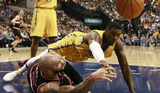 Chicago Bulls forward Carlos Booozer, left, passes the basketball as Indiana Pacers center Ian Mahinmi dives for it in the first half of an NBA basketball game in Indianapolis, Friday, March 21, 2014. (AP Photo/R Brent Smith)