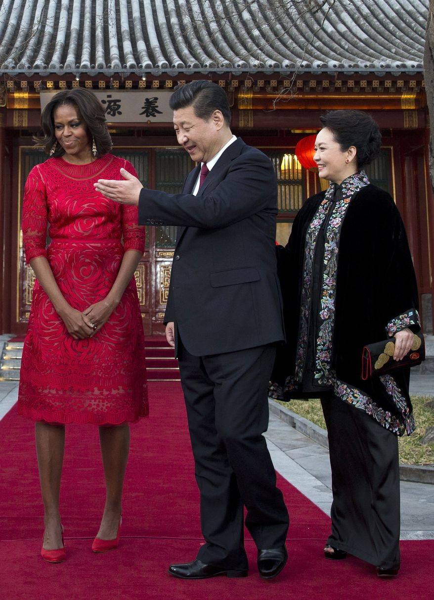 Chinese President Xi Jinping, center, and his wife Peng Liyuan, right, show the way to U.S. first lady Michelle Obama as they proceed to a meeting room at the Diaoyutai state guesthouse in Beijing, China Friday, March 21, 2014. (AP Photo/Andy Wong, Pool)