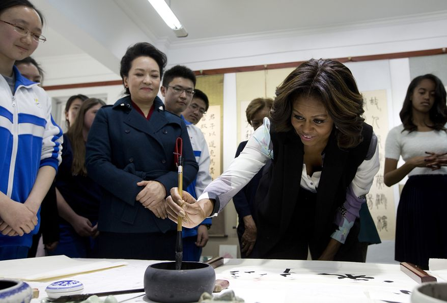 U.S. first lady Michelle Obama dip a brush in an ink pod as she tries out writing Chinese charactors as Peng Liyuan, wife of Chinese President Xi Jinping, left, watches her during their visit in a Chinese traditional calligraphy class at the Beijing Normal School, a school that prepares students to go abroad in Beijing, China Friday, March 21, 2014. (AP Photo/Andy Wong, Pool)