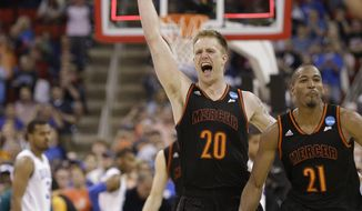 Mercer forward Jakob Gollon (20) and guard Langston Hall (21) celebrate after defeating Duke 78-71 in an NCAA college basketball second-round game against Duke, Friday, March 21, 2014, in Raleigh, N.C.(AP Photo/Gerry Broome)