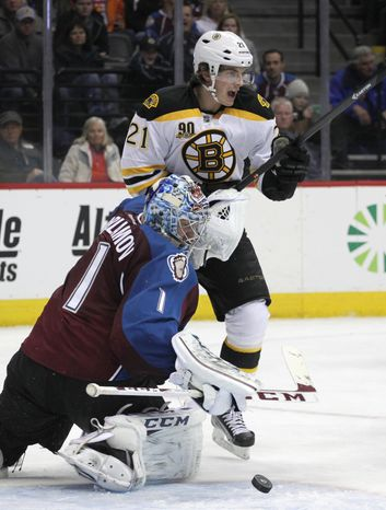 Colorado Avalanche goalie Semyon Varlamov (1) watches the puck bounce out of the net as Boston Bruins left wing Loui Eriksson (21) reacts to the goal scored by Carl Soderberg in the second period of an NHL hockey game in Denver on Friday, March 21, 2014.(AP Photo/Joe Mahoney)