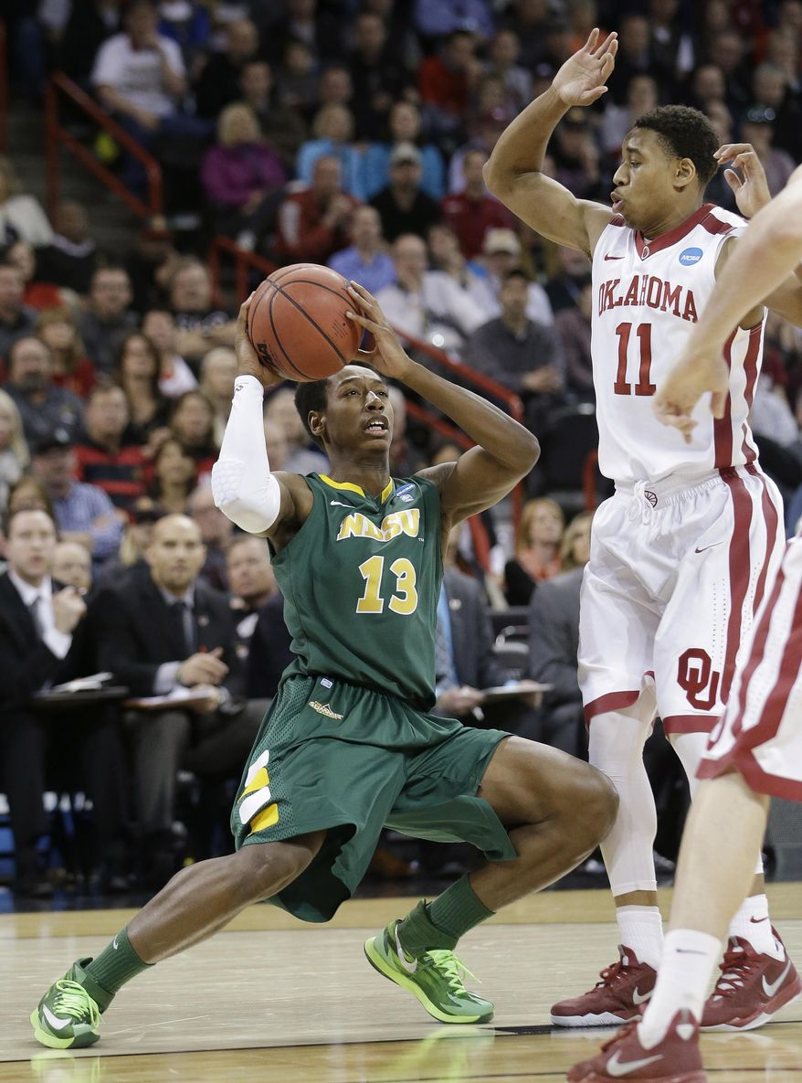 North Dakota State's Carlin Dupree (13) looks for a shot as Oklahoma's Isaiah Cousins defends in overtime during a second-round game of the NCAA men's college basketball tournament in Spokane, Wash., Thursday, March 20, 2014. North Dakota State won 80-75 in overtime. (AP Photo/Elaine Thompson)