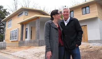 Architect Louis Cherry and his wife, Marsha Gordon, stand in front of their new home in the Historic Oakwood neighborhood of Raleigh, N.C., on Sunday, March 16, 2014. The couple may have to demolish the unfinished home because of a neighbor's challenge that the house doesn't meet guidelines for the historic district. (AP Photo/Allen G. Breed)