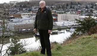 ADVANCE FOR USE MONDAY, MARCH 24, 2014 AT 3 A.M. AND THEREAFTER - Jack Durney, mayor of Hoquiam, Wash., stands on a hill on Monday, March 18, 2014, overlooking his city, the Hoquiam River, and Grays Harbor. Because most of Hoquiam lies in the flood plain, Durney says possible increases in federal flood insurance rates would adversely affect many who live in his town. In the old logging port on an estuarine bay, the great majority of the 8,700 residents live in a flood hazard area. (AP Photo/Ted S. Warren)