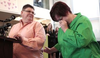 Jayne Rowse, left, looks at April DeBoer as she reacts during a news conference in Ferndale, Mich., Friday, March 21, 2014. A federal judge  struck down Michigan's ban on gay marriage Friday, the latest in a series of decisions overturning similar laws across the U.S. The two nurses who've been partners for eight years claimed the ban violated their rights under the U.S. Constitution. (AP Photo/Paul Sancya)