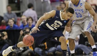 George Washington guard Joe McDonald (22) moves the ball against Memphis guard Geron Johnson (55) during the first half of an NCAA college basketball second-round tournament game, Friday, March 21, 2014, in Raleigh. (AP Photo/Chuck Burton)