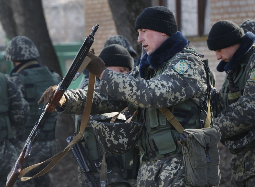 Ukrainian border guards prepare for training at a military camp in the village of Alekseyevka on the Ukrainian-Russian border, eastern Ukraine, Friday, March 21, 2014. Russian President Vladimir Putin has signed a resolution approved by parliament to annex Crimea. (AP Photo/Sergei Grits)