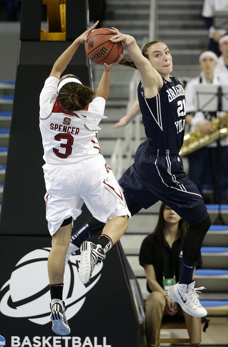 BYU's Lexi Eaton, right, blocks a shot by North Carolina State's Miah Spencer during the first half of a first-round game in the NCAA women's college basketball tournament on Saturday, March 22, 2014, in Los Angeles. (AP Photo/Jae C. Hong)