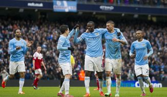 Manchester City's Yaya Toure, centre, celebrates with teammates after scoring his third goal against Fulham during their English Premier League soccer match at the Etihad Stadium, Manchester, England, Saturday March 22, 2014. (AP Photo/Jon Super)