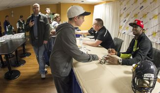 New York Jets quarterback Geno Smith, right, greets fans and signed autographs at the Charleston Civic Center Saturday, March 22, 2014 in Charleston, WV. (AP Photo/Michael Switzer)