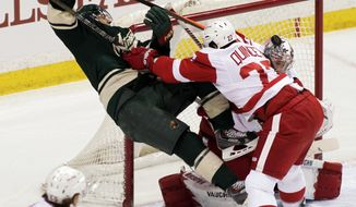Minnesota Wild left wing Zach Parise (11) is checked hard by Detroit Red Wings defenseman Kyle Quincey (27) during the first period of an NHL hockey game, Saturday, March 22, 2014, in St. Paul, Minn. (AP Photo/Paul Battaglia)