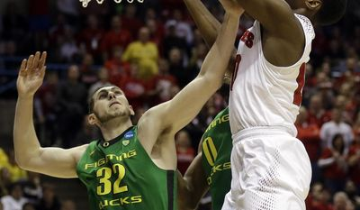 Wisconsin forward Nigel Hayes grabs a rebound against Oregon forward Ben Carter (32) during the first half of a third-round game of the NCAA college basketball tournament Saturday, March 22, 2014, in Milwaukee. (AP Photo/Jeffrey Phelps)