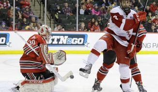 Ohio State goalie Christian Frey (30) deflects a shot as Wisconsin forward Tyler Barnes, right, jumps out of the way during the second period of the championship college hockey game of the Big 10 Conference tournament in St. Paul, Minn., Saturday, March 22, 2014. (AP Photo/Ann Heisenfelt)
