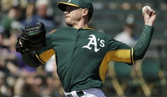 Oakland Athletics starting pitcher Scott Kazmir throws to the Seattle Mariners during the first inning of a spring exhibition baseball game in Phoenix, Saturday, March 22, 2014. (AP Photo/Chris Carlson)
