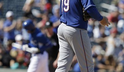 Texas Rangers' Tommy Hanson rubs a new baseball after giving up a home run to Kansas City Royals' Justin Maxwell during the fifth inning of a spring exhibition baseball game, Saturday, March 22, 2014, in Surprise, Ariz. (AP Photo/Darron Cummings)