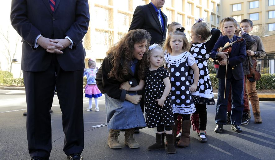 In this March 14, 2014, file photo, the Rev. Mark Harris, left, who is seeking a Republican U.S. Senate nomination in the upcoming North Carolina primary, was supported during a campaign event by Michelle Duggar, kneeling, and Jim Bob Duggar, back right, and many of the Duggars' 19 children, in Raleigh, N.C. (AP Photo/Ted Richardson) ** FILE **