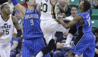 Utah Jazz's Gordon Hayward (20) goes to the basket as Orlando Magic's Nikola Vucevic (9), of Montenegro, and Ronnie Price (10) defend in the second quarter during an NBA basketball game on Saturday, March 22, 2014, in Salt Lake City. (AP Photo/Rick Bowmer)