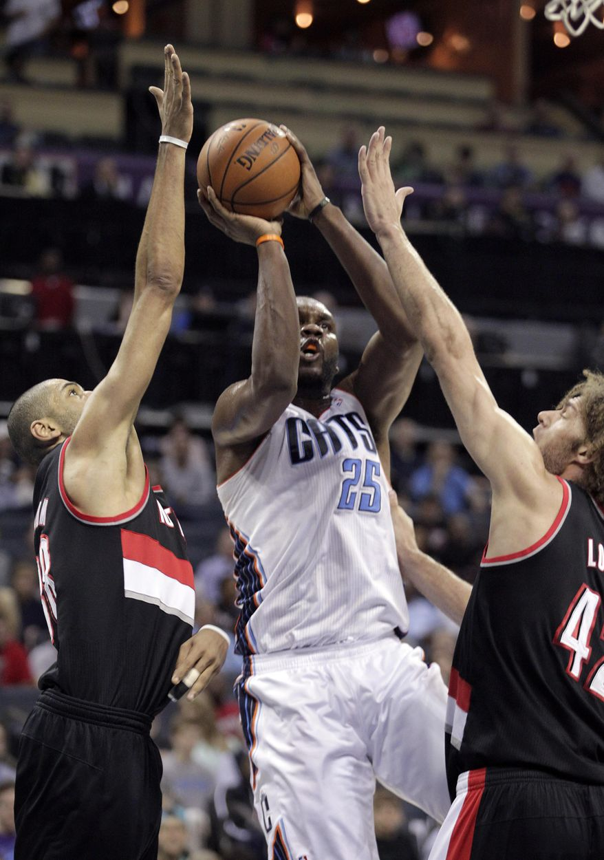 Charlotte Bobcats' Al Jefferson, middle, aims his short jumper through the defense of Portland Trail Blazers' Nicolas Batum, left, and Robin Lopez, right, during the first half of an NBA basketball game in Charlotte, N.C., Saturday, March 22, 2014. (AP Photo/Bob Leverone)