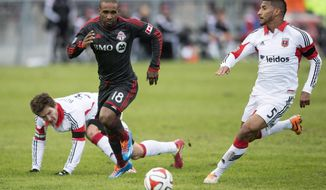 Toronto FC 's Jermain Defoe (18) drives between D.C. United's Bobby Boswell, left, and Sean Franklin during the second half of an MLS soccer game in Toronto on Saturday, March 22, 2014. (AP Photo/The Canadian Press, Chris Young)
