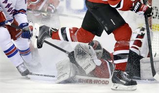 New Jersey Devils goalie Martin Brodeur falls in front of the goal as he blocks a shot during the first period of an NHL hockey game against the New York Rangers on Saturday, March 22, 2014, in Newark, N.J. (AP Photo/Mel Evans)
