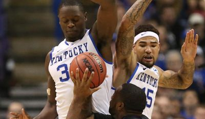 Kentucky forwards Julius Randle (left) and Willie Cauley-Stein defend against Kansas State forward Thomas Gipson in second half action during a Second Round NCAA Tournament game between Kansas State and Kentucky on Friday, March 21, 2014, at the Scottrade Center in St. Louis. (AP Photo/St. Louis Post-Dispatch, Chris Lee)