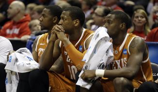 Texas' Prince Ibeh, left, Texas forward Jonathan Holmes and Kendal Yancy watch from the bench during the second half of a third-round game against the Michigan of the NCAA college basketball tournament Saturday, March 22, 2014, in Milwaukee. Michigan won 79-65. (AP Photo/Morry Gash)