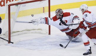 Carolina Hurricanes goaltender Cam Ward (30) sticks-saves the shot from Winnipeg Jets' Bryan Little as Hurricanes' Riley Nash (20) watches during the first period of an NHL hockey game, Saturday, March 22, 2014, in Winnipeg, Manitoba. (AP Photo/The Canadian Press, John Woods)
