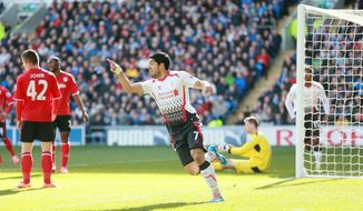 Liverpool's Luis Suarez, center, celebrates scoring Liverpool's first goal during their English Premier League soccer match against Cardiff at Cardiff City Stadium, Cardiff, Wales, Saturday, March 22, 2014. (AP Photo/David Davies, PA Wire)    UNITED KINGDOM OUT   -   NO SALES  -   NO ARCHIVES