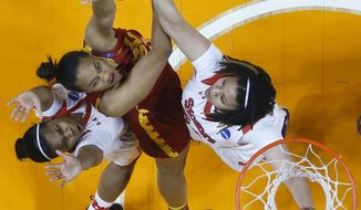 Southern California forward Alexyz Vaioletama, center, shoots as she is defended by St. John's Keylantra Langley, left, and Selina Archer, right, in the first half of an NCAA women's college basketball first-round tournament game, Saturday, March 22, 2014, in Knoxville, Tenn. (AP Photo/Mark Humphrey)