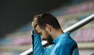 FC Barcelona's Gerard Pique touches his head during a training session at the Sports Center FC Barcelona Joan Gamper in San Joan Despi, Spain, Saturday, March 22, 2014.  Real Madrid will play against FC Barcelona in a Spanish La Liga soccer match next Sunday 23 March. (AP Photo/Manu Fernandez)