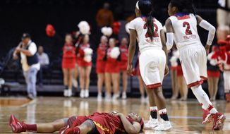 Southern California guard Brianna Barrett lies on the court as St. John's Eugeneia McPherson (22) and Amber Thompson (2) run to their teammates after Barrett missed a 3-point shot attempt as time ran out in the second half of an NCAA women's college basketball first-round tournament game Saturday, March 22, 2014, in Knoxville, Tenn. St. John's won 71-68. (AP Photo/Mark Humphrey)