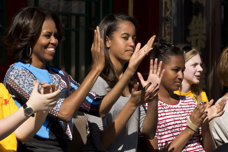 From left to right, U.S. first lady Michelle Obama, and her daughters Malia, second right, and Sasha applaud as they watch a Peking opera performance with a group of American schoolchildren who are visiting China during their spring break, at the Summer Palace in Beijing, Saturday, March 22, 2014. (AP Photo/Alexander F. Yuan)