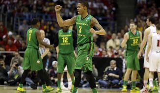 Oregon guard Joseph Young (3) reacts to a foul call against Wisconsin during the first half of a third-round game of the NCAA college basketball tournament Saturday, March 22, 2014, in Milwaukee. (AP Photo/Jeffrey Phelps)