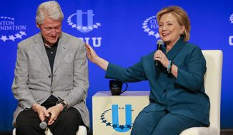 Former President Bill Clinton, left, listens as former Secretary of State Hillary Rodham Clinton speaks during a student conference for the Clinton Global Initiative University, Saturday, March 22, 2014, at Arizona State University in Tempe, Ariz. More than 1,000 college students are gathered at Arizona State University this weekend as part of the Clinton Global Initiative University's efforts to advance solutions to pressing world challenges. (AP Photo/Matt York)