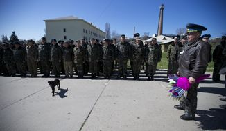 Colonel Yuly Mamchur, right, holds flowers as other Ukrainian airmen line up to greet their comrades who arrived to celebrate their wedding at the Belbek airbase outside Sevastopol, Crimea, on Saturday, March 22, 2014. Two young Lieutenants, medic Galina Volosyanchik and communication officer Ivan Benera got married today and arrived to their unit for a short celebration as Russian troops continue to occupy part of the airbase and demand surrender of Ukrainian airmen. (AP Photo/Ivan Sekretarev)