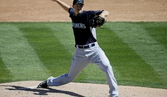 Seattle Mariners starting pitcher Scott Baker throws to the Oakland Athletics during the third inning of a spring exhibition baseball game in Phoenix, Saturday, March 22, 2014. (AP Photo/Chris Carlson)