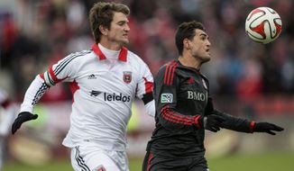 Toronto FC's Gilberto Olivera Sousa Jr., right, shields the ball from D.C. United's Bobby Boswell during the first half of an MLS soccer game in Toronto on Saturday, March 22, 2014. (AP Photo/The Canadian Press, Chris Young)
