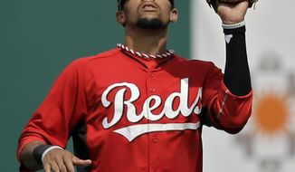 Cincinnati Reds center fielder Billy Hamilton catches a fly ball off the bat of Milwaukee Brewers' Khris Davis in the second inning of a spring exhibition baseball game Sunday, March 23, 2014, in Goodyear, Ariz. (AP Photo/Mark Duncan)