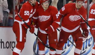 Detroit Red Wings' Gustav Nyquist (14) is congratulated by teammates Niklas Kronwall (55) and Joakim Andersson (18), all of Sweden, during the first period of an NHL hockey game against the Minnesota Wild Sunday, March 23, 2014 in Detroit. (AP Photo/Duane Burleson)