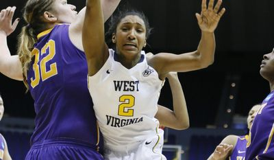 West Virginia guard Taylor Palmer (2) goes airborne after being fouled by Albany center Megan Craig (32) in the second half of an NCAA college basketball first-round tournament game on Sunday, March 23, 2014, in Baton Rouge, La. West Virginia won 76-61. (AP Photo/Rogelio V. Solis)