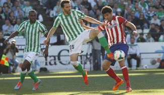 Atletico de Madrid's Diego Costa, right, and Betis'  Jordi Figueras , centre, fight for the ball as Betis' Paulao Santos, right, looks on during their La Liga soccer match at the Benito Villamarin stadium, in Seville, Spain on Sunday, March 23, 2014. (AP Photo/Angel Fernandez)