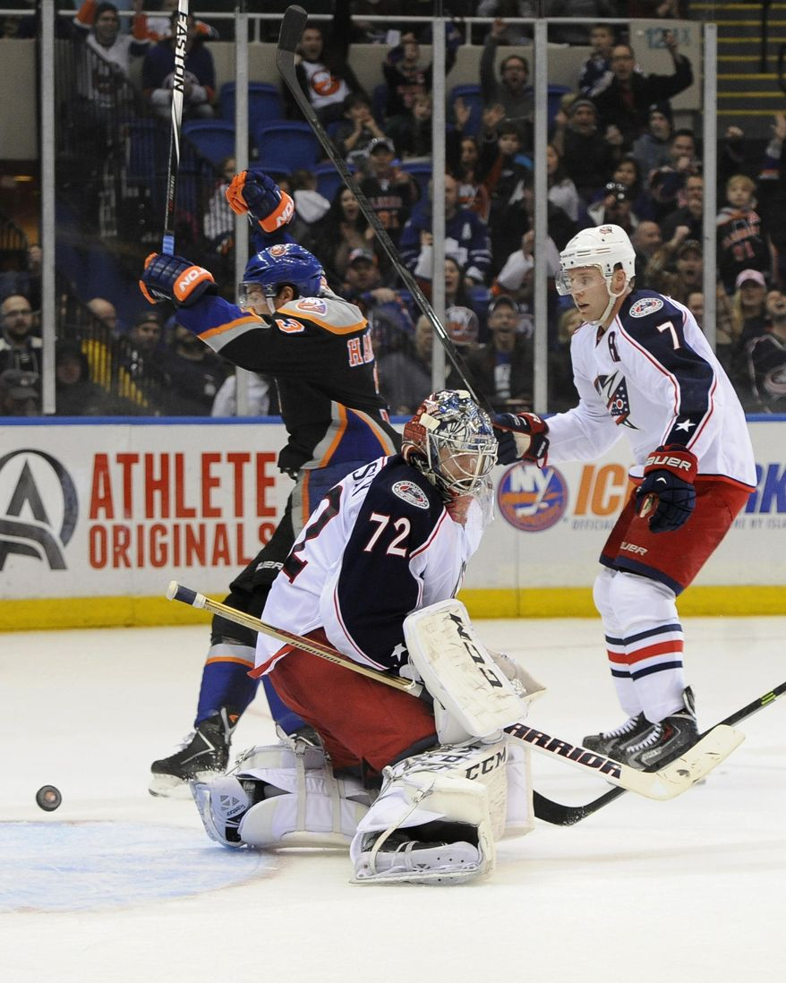 New York Islanders' Travis Hamonic (3)  celebrates his goal as Columbus Blue Jackets goalie Sergei Bobrovsky (72) and  Jack Johnson (7) react in the second period of an NHL hockey game, Sunday, March 23, 2014, in Uniondale, N.Y. (AP Photo/Kathy Kmonicek)