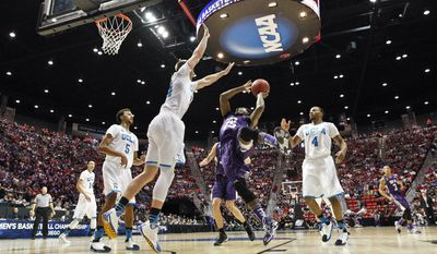 Stephen F. Austin guard Desmond Haymon, center, attempts a fall away shot as UCLA forward Travis Wear, center left, tries for the block during the first half of a third-round game in the NCAA college basketball tournament, Sunday, March 23, 2014, in San Diego. (AP Photo/Gregory Bull )